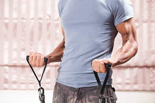 Slim Muscular male using resistance bands at home. bicep curl stock photo
