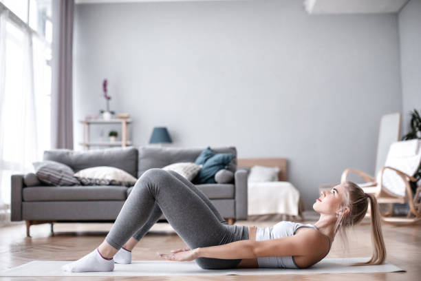 Slim sporty girl doing abs workout at home. stock photo