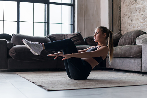 istock Slim sporty girl doing v-ups abs workout at home 689890106