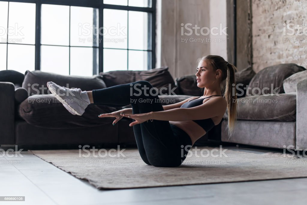 Slim sporty girl doing v-ups abs workout at home stock photo