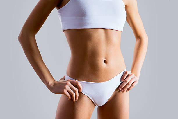 slim tanned woman's body - midsection stock pictures, royalty-free photos & images