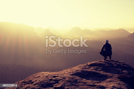 Hiker sits on a rocky peak and enjoy the scenerySlim tourist on the sharp peak of rock in rock empires park  is watching over the misty and foggy morning valley to Sun