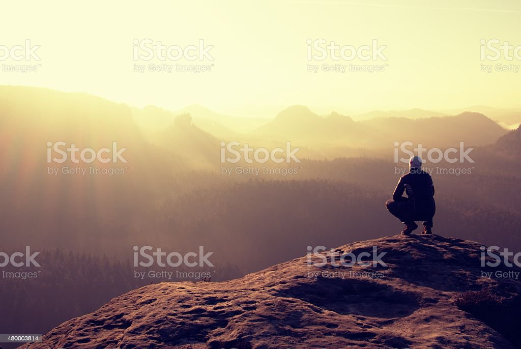Slim tourist on peak of rock in autumn empires park stock photo