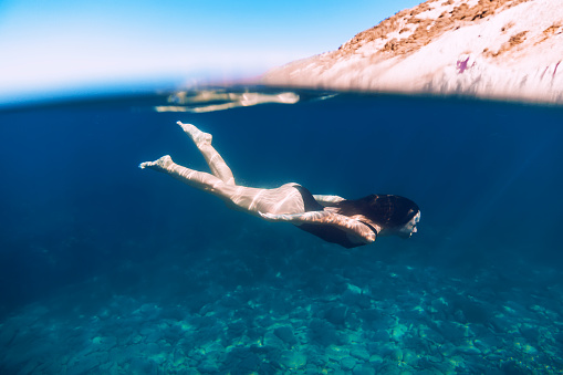 888067280 istock photo Slim woman and bikini swimming in ocean, dive underwater blue sea 900827780