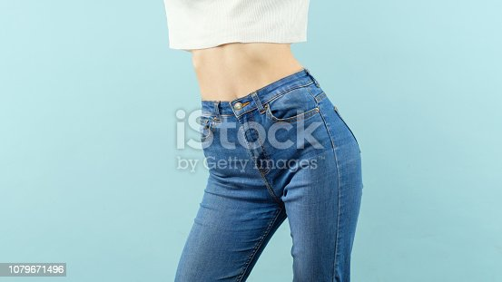 slim woman midsection in cropped t-shirt and high-waist denim on blue background. female shape and fitness