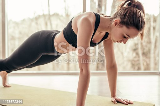 istock Slim woman doing plank exercise in gym 1178672344