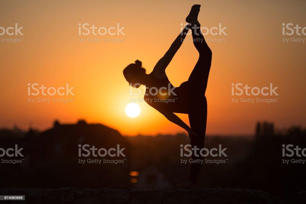 Slim woman doing yoga over orange sun royalty-free stock photo