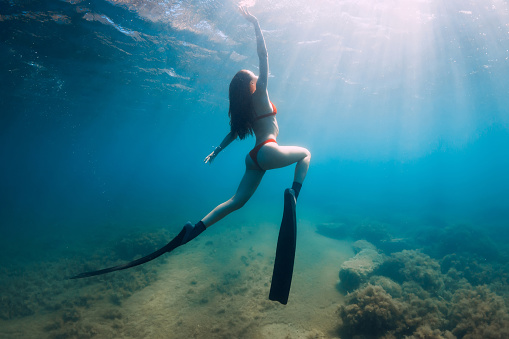 istock Slim woman freediver posing  underwater in blue sea with sun rays. Freediving with fins in sea 1269337769