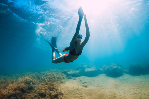 istock Slim woman in bikini glides at blue sea with sun rays. Freediving with fins underwater in sea 1269337669