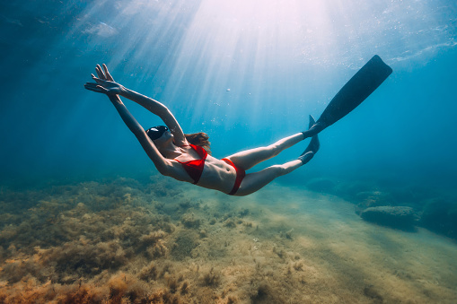 istock Slim woman in bikini glides at blue sea with sun rays. Freediving with fins underwater in sea 1269337721