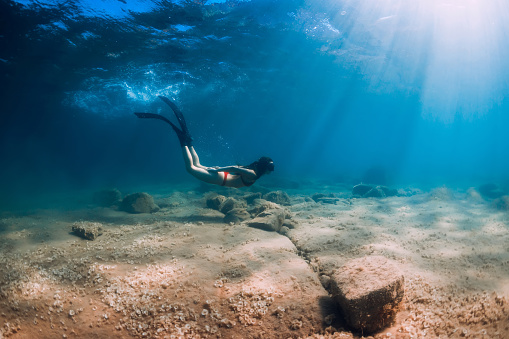 istock Slim woman in bikini glides at blue sea with sun rays. Freediving with fins underwater in sea 1269337743