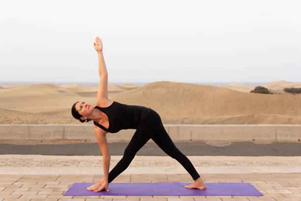 Slim woman in black sportswear practicing parivrtta trikonasana by Maspalomas sand dunes stock photo