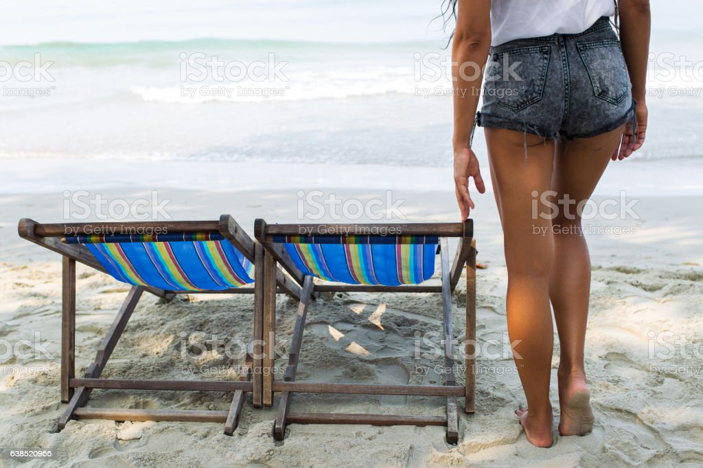 Slim woman in jeans short standing near chaise-lounge stock photo