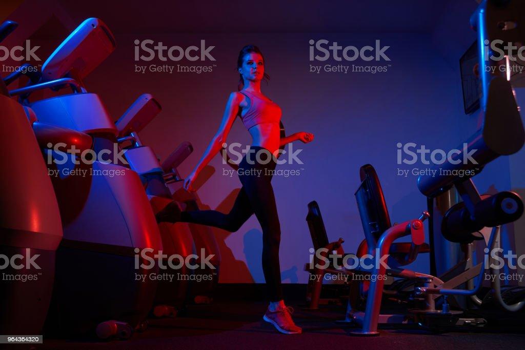 Slim mulher saltando entre linhas de máquinas de exercício - Foto de stock de Adulto royalty-free