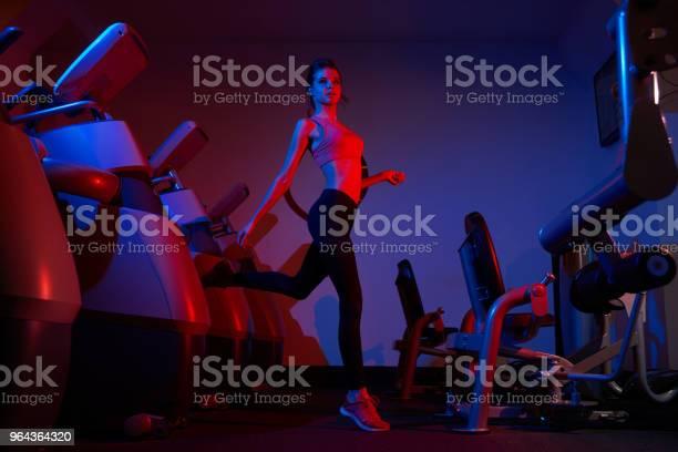 Foto de Slim Mulher Saltando Entre Linhas De Máquinas De Exercício e mais fotos de stock de Adulto