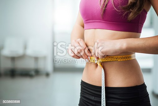istock Slim woman measuring her thin waist 503865898