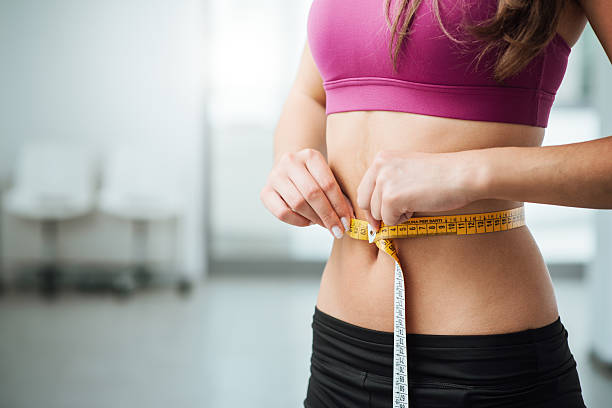 slim woman measuring her thin waist - human abdomen stock pictures, royalty-free photos & images