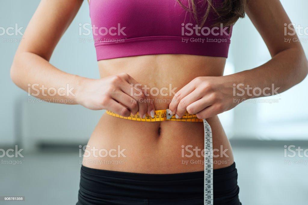 Delgada mujer medir su cintura delgada - foto de stock