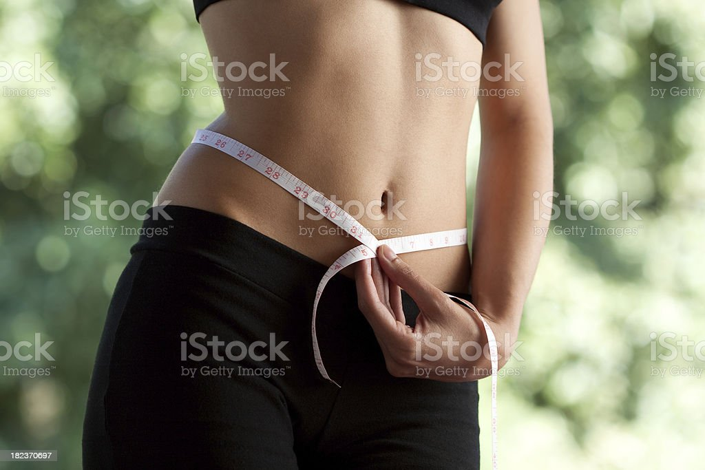 Slim woman measuring waist stock photo