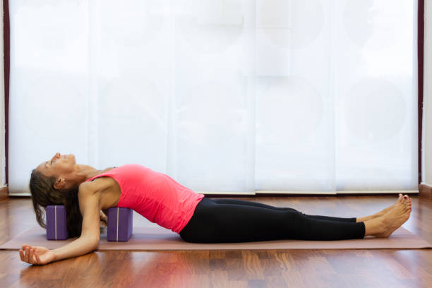 Slim woman rests back and head on blocks at yoga studio stock photo