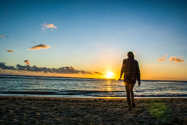 Slim woman walks towards the ocean whilst sunsets stock photo