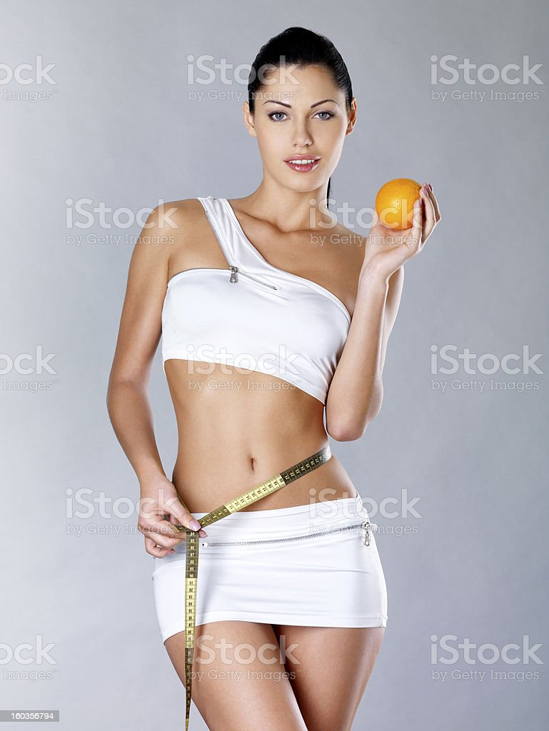 Slim young woman in white holding an orange & measuring tape stock photo