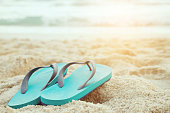 slipper of foot in sandals shoes and Blue ocean wave water distribution on sandy white beach, Sea background.The color of the water and beautifully bright. travel nature holiday summer concept.