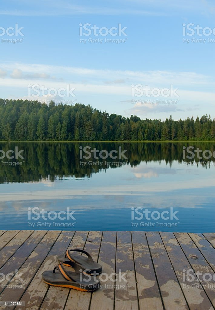 slippers on a pier of the lake royalty-free stock photo