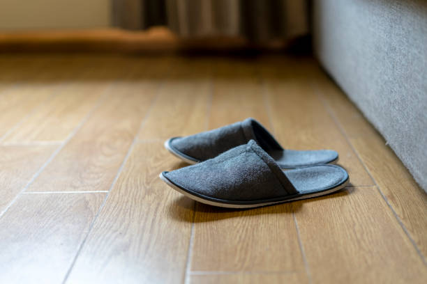 slippers on floor beside sofa stock photo