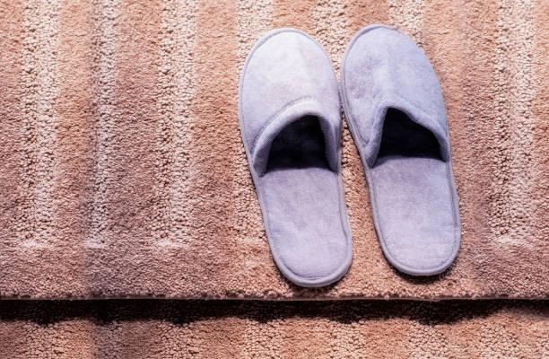 Slippers on the carpet. Soft comfortable home slipper stock photo