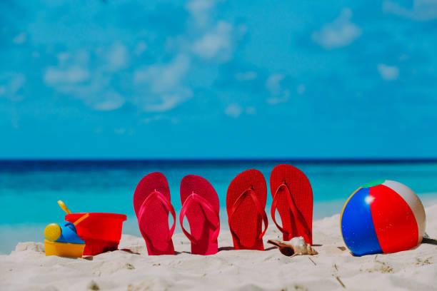 hausschuhe, spielzeug und tauchmaske am strand - flitterwochen flip flops stock-fotos und bilder