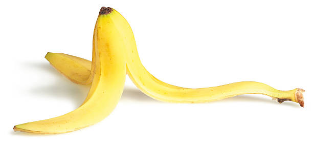 A slippery banana on a white background  slippery banana skin on a white background banana peel stock pictures, royalty-free photos & images