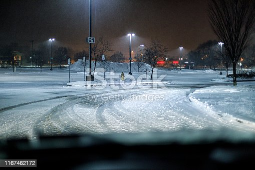 Car driver perspective approaching a headlights illuminated, slippery, slushy tire tracked curve during a frigid, extreme weather, whipping wind, winter blizzard snow storm in a late night supermarket shopping mall parking lot near Rochester, New York State in early January. Part of a