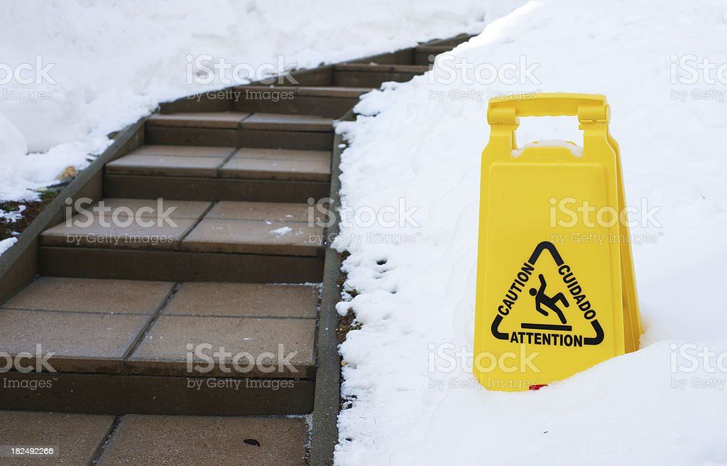 Slippery path in winter with caution sign stock photo