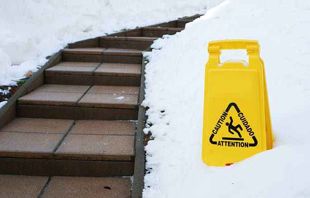 Slippery path in winter with caution sign Slippery path in winter with caution sign slippery stock pictures, royalty-free photos & images