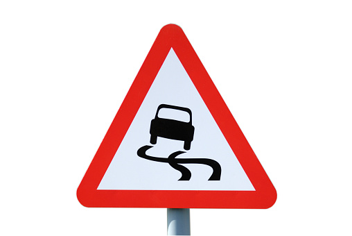 Triangular warning sign of slippy road conditions ahead for motorists.