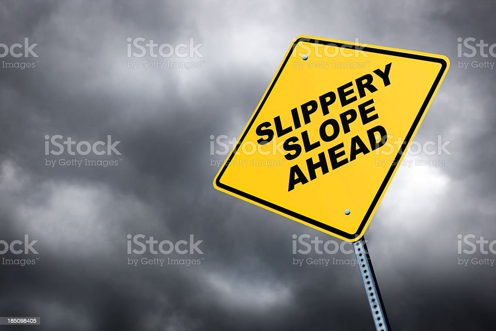 Slippery Slope  road sign in front of cloudy sky background stock photo