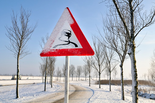 Frozen slippery road sign in front of a snowy icy road.