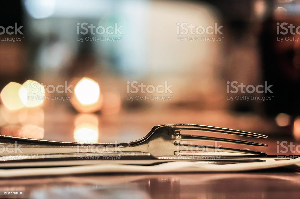Sliver fork on table with blur lights behind stock photo