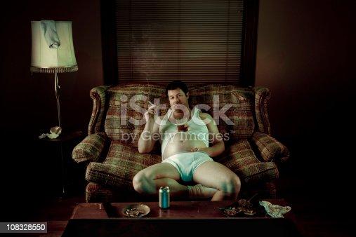 istock Slob Man watching television while smoking in underwear 108328550