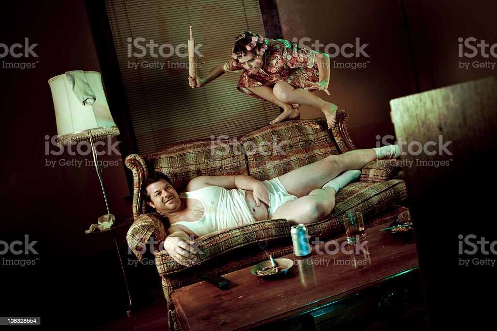 Slob Man watching television while woman pounces with rolling pin stock photo