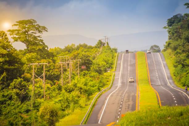helling snelweg met zonneschijn en groene verkeerseiland. vier-baans snelweg met groene verkeerseiland. de provinciale immense weg langs een groen bos. - parallel stockfoto's en -beelden