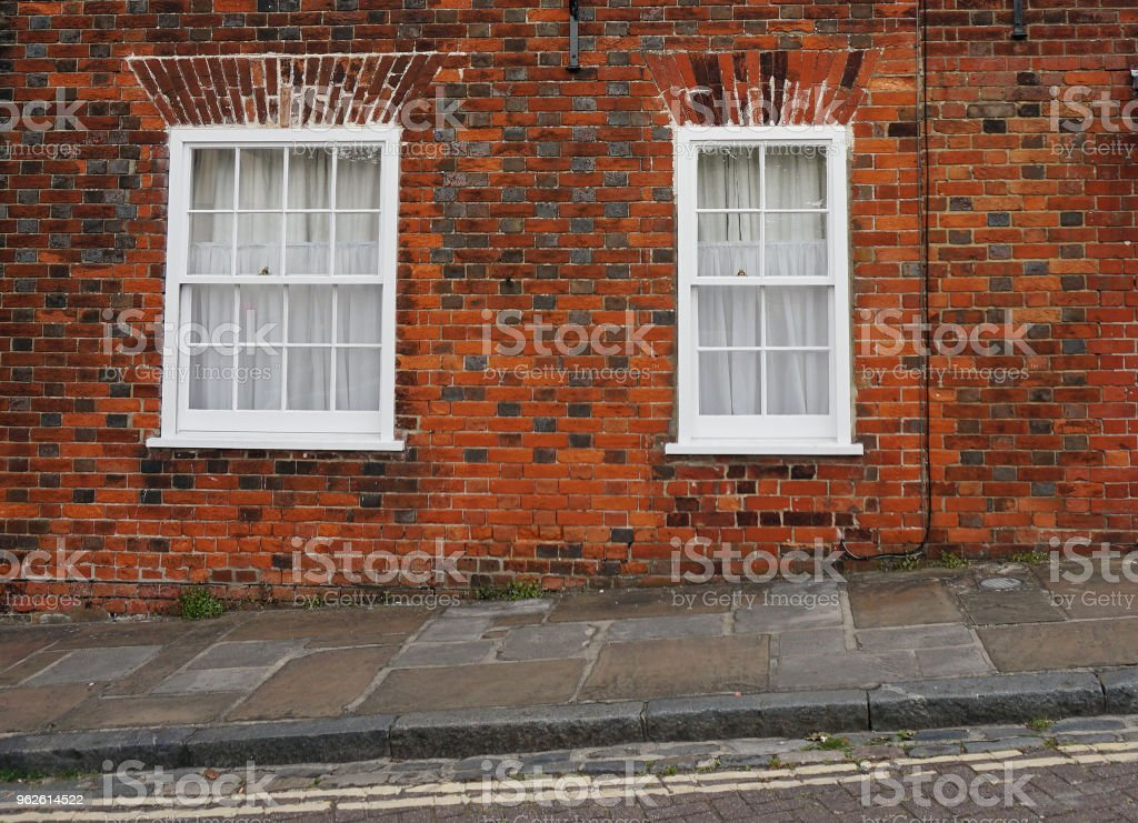 Sloped street with two windows on a brick facade. stock photo