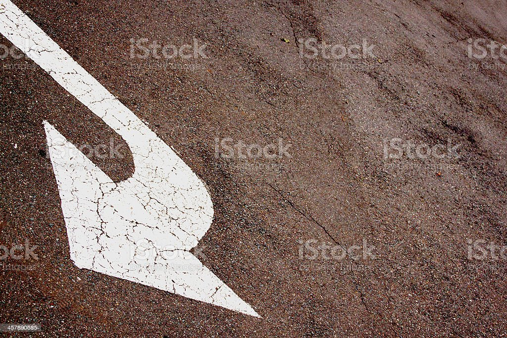 Sloping White Painted Arrow On Tarmac Road Surface stock photo