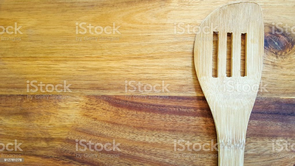 Slotted wooden spoon on a cutting board in the kitchen stock photo