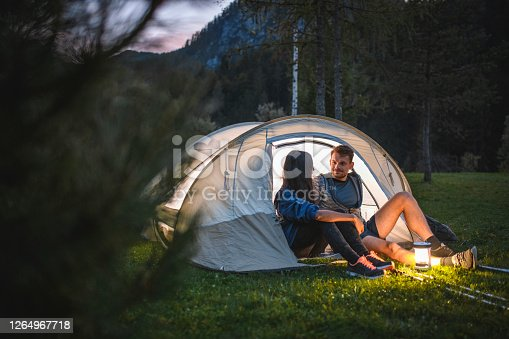 Smiling young camping couple sitting on tent porch and talking at dusk near alpine town of Kranjska Gora in northwestern Slovenia.