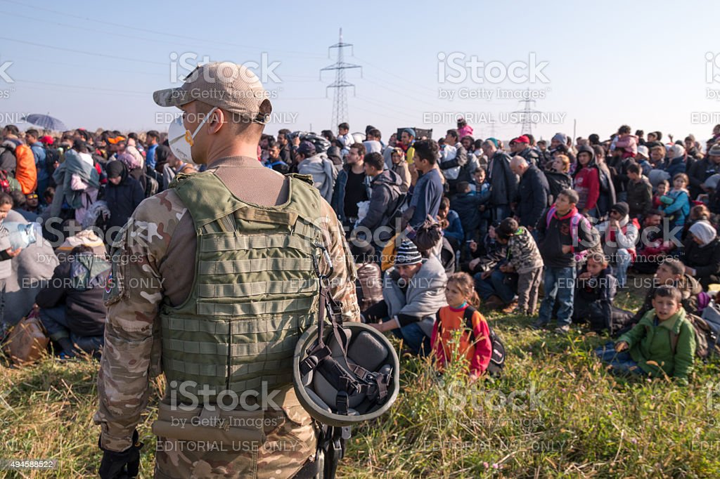 Slovenian Soldier Guarding The Refugee Group Stock Photo - Download