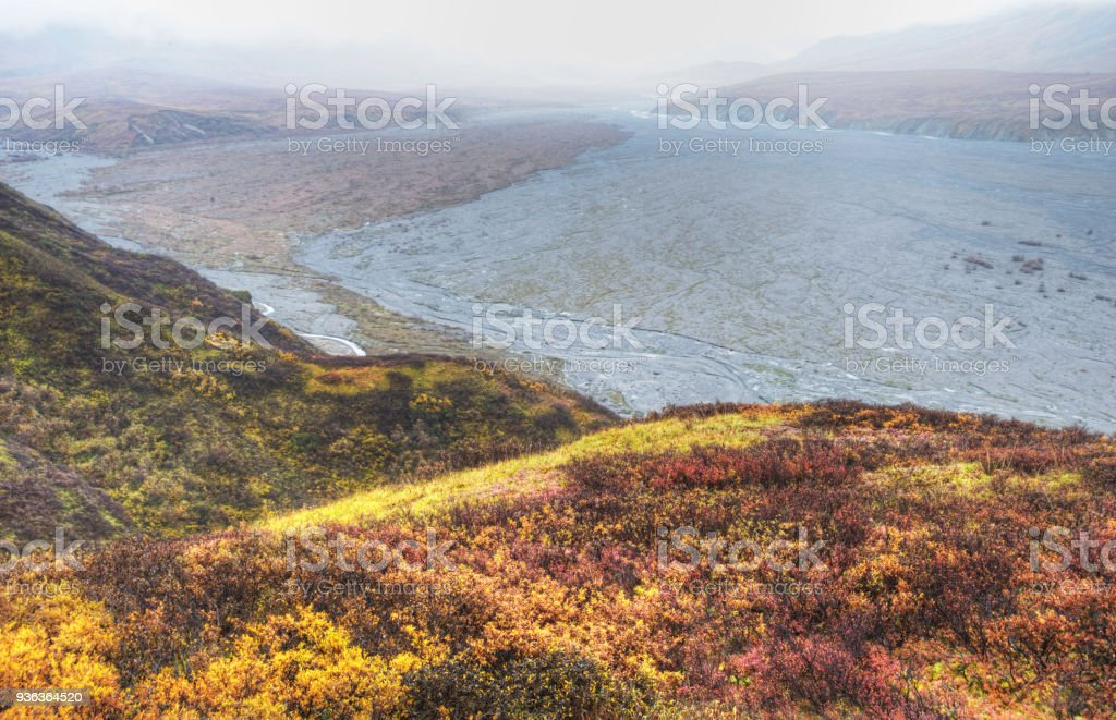 A slow braided river in Alaska winds the way through mountains covered with Blueberry Bushes in fall. stock photo