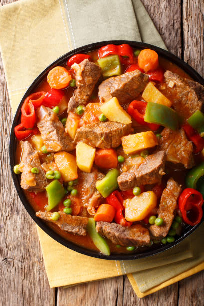 Slow cooked beef with potatoes, peppers, peas, tomatoes and carrots in a spicy sauce close-up. Vertical top view stock photo