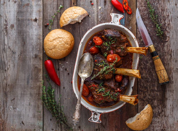 Slow cooked lamb shanks with tomato and herds, copy space stock photo